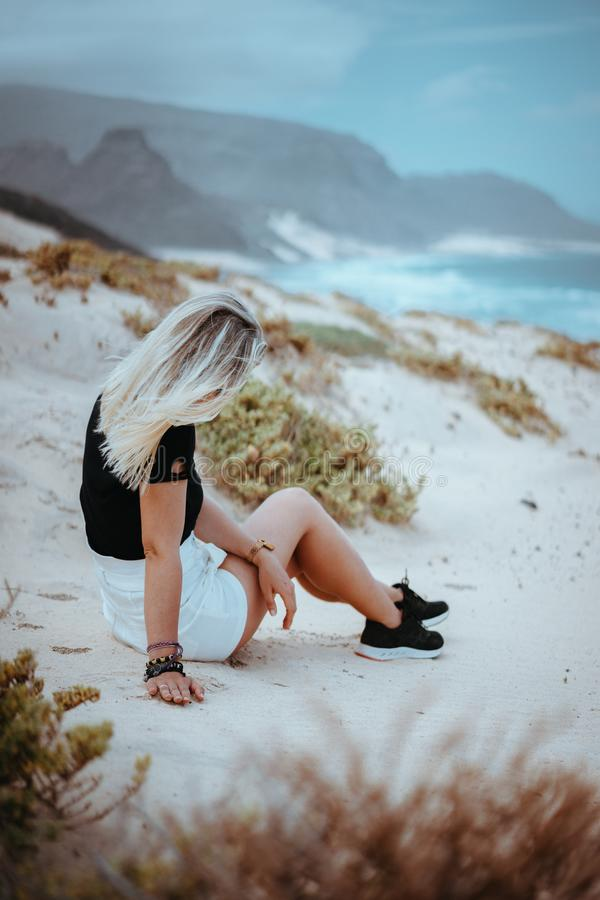 Young woman sitting on white sand dune surrounded by barren desert vegetation. Atlantic ocean coastline in background stock photography
