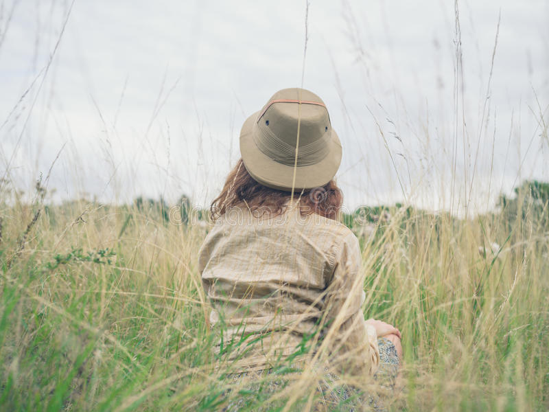 Young woman sitting in wilderness stock photos
