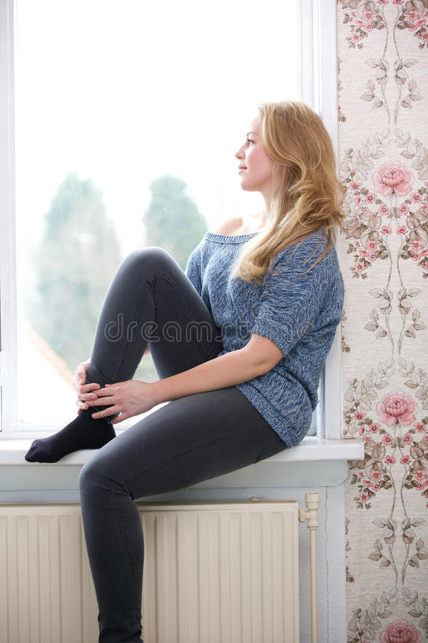 Young woman sitting on windowsill at home stock photo