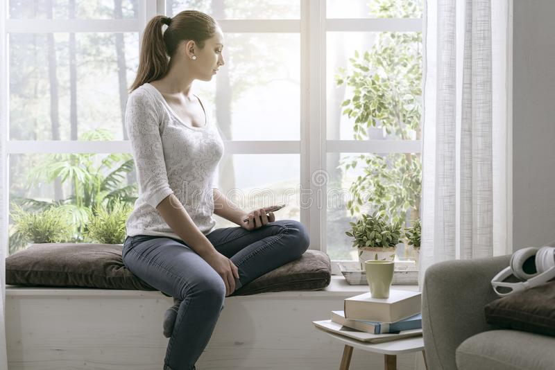 Young woman sitting on the windowsill and using her phone royalty free stock photos