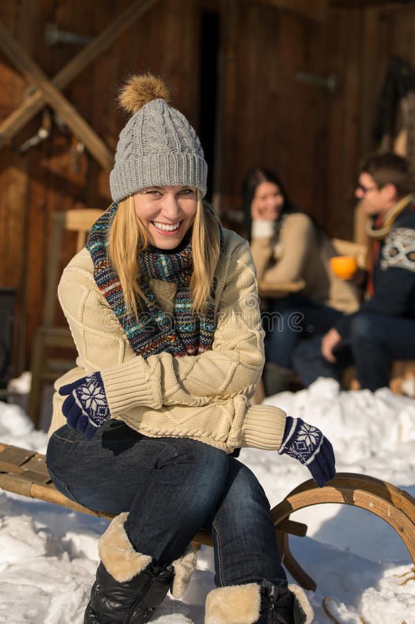 Young woman sitting winter snow sledge cottage stock photo