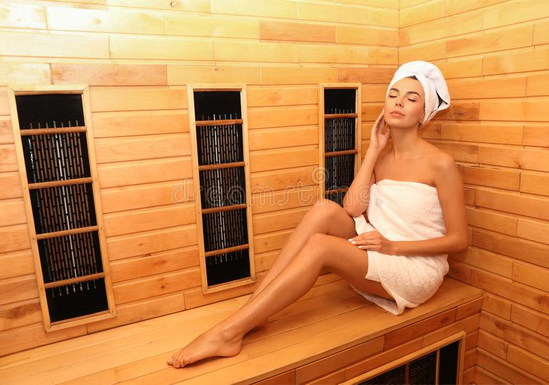 Young woman sitting on wooden bench in infrared sauna. Spa treatment. Young woman sitting on wooden bench in infrared sauna, space for text. Spa treatment stock photo