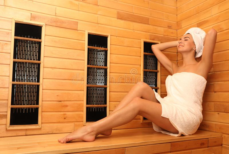 Young woman sitting on wooden bench in infrared sauna,. Spa treatment. Young woman sitting on wooden bench in infrared sauna, space for text. Spa treatment royalty free stock image