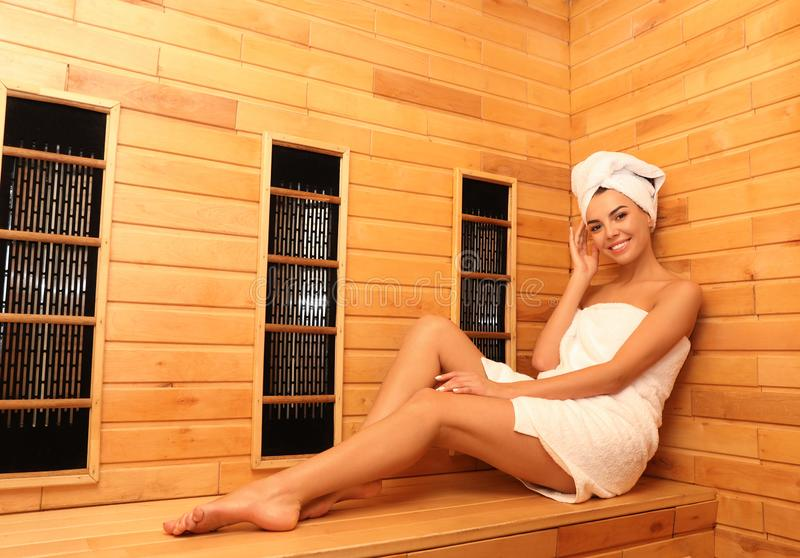 Young woman sitting on wooden bench in infrared sauna. Spa treatment royalty free stock photography