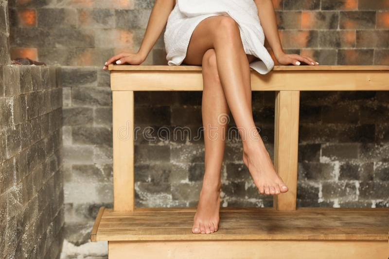 Young woman sitting on wooden bench in salt sauna. Spa treatment. Young woman sitting on wooden bench in salt sauna, closeup. Spa treatment stock image