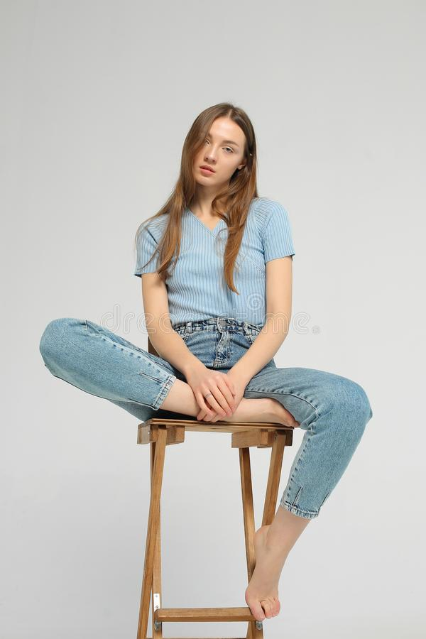 Young woman is sitting on wooden chair in studio royalty free stock photography