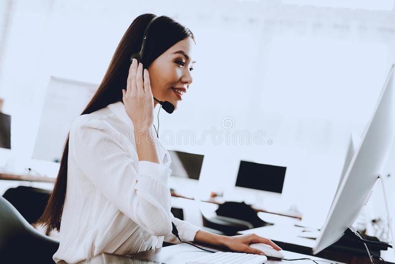 Young Woman Sitting and Working in Call Center. Manager with Computer. Girl on Workplace. Consultant with Microphone. Customer royalty free stock image