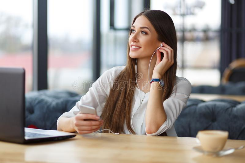 A young woman at the working place. A young woman is sitting at the working place, enjoying the music in her ear-phones stock images