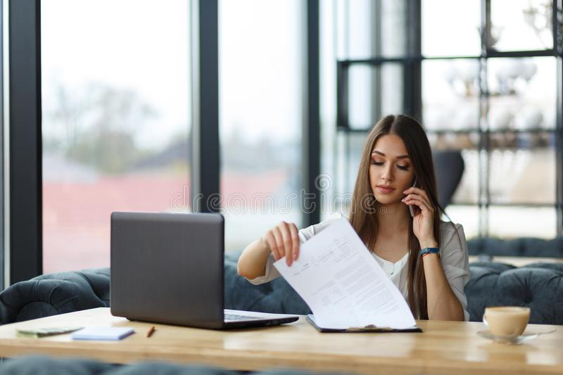 A young woman at the working place. A young woman is sitting at the working place, talking on the phone and looking through the documents stock photos
