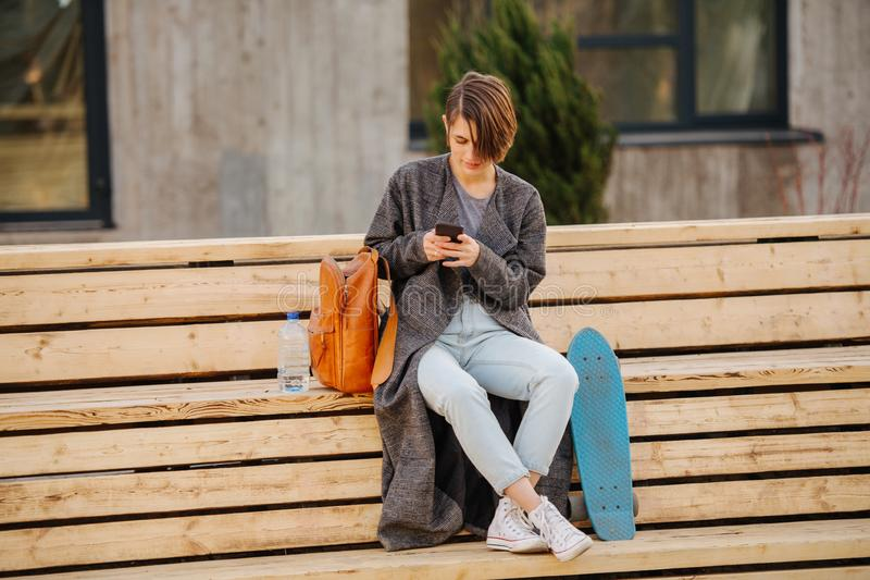 Young woman with a skateboard is resting on a 2 stage bench. lifestyle photo. A young woman with short hair in grey fashionable coat with a skateboard is stock images