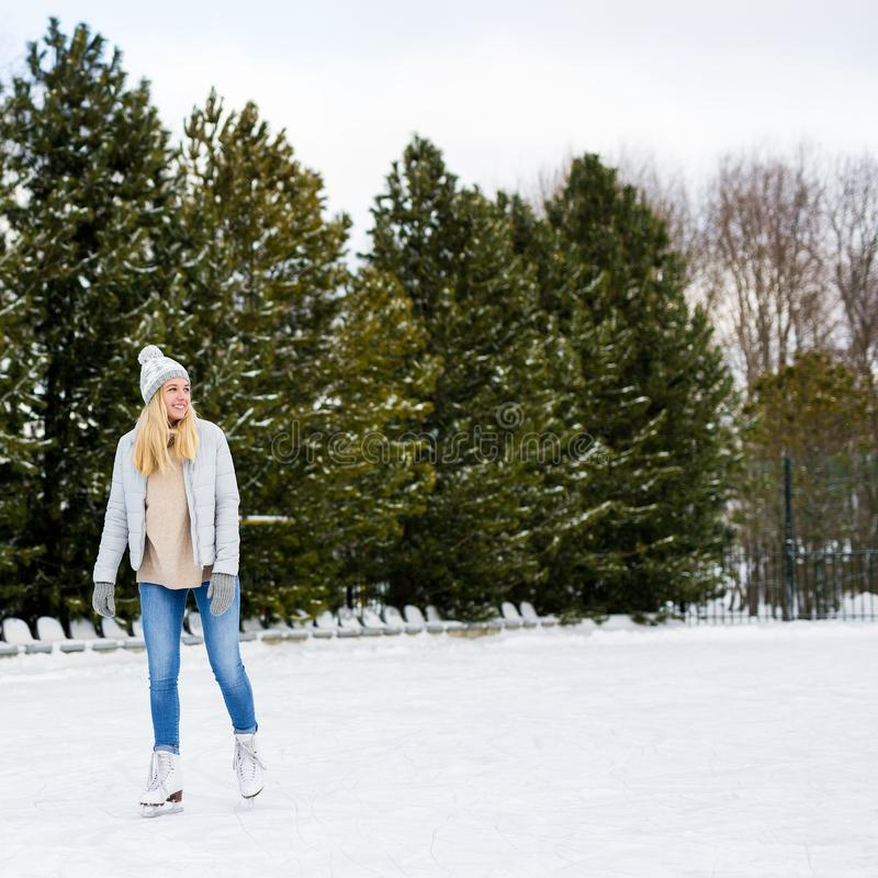 Young woman skating on ice with figure skates outdoors. Happy young woman skating on ice with figure skates outdoors royalty free stock images