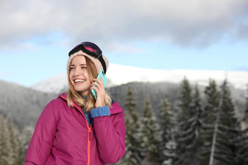 Young woman with ski goggles talking on phone in mountains during winter vacation. Space for text stock images