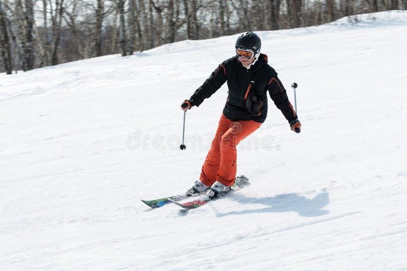 Young woman skier coming down the slope on sunny day. MOROZNAYA MOUNTAIN, YELIZOVO, KAMCHATKA, RUSSIA - APRIL 17, 2015: Young woman skier coming down the slope royalty free stock photography