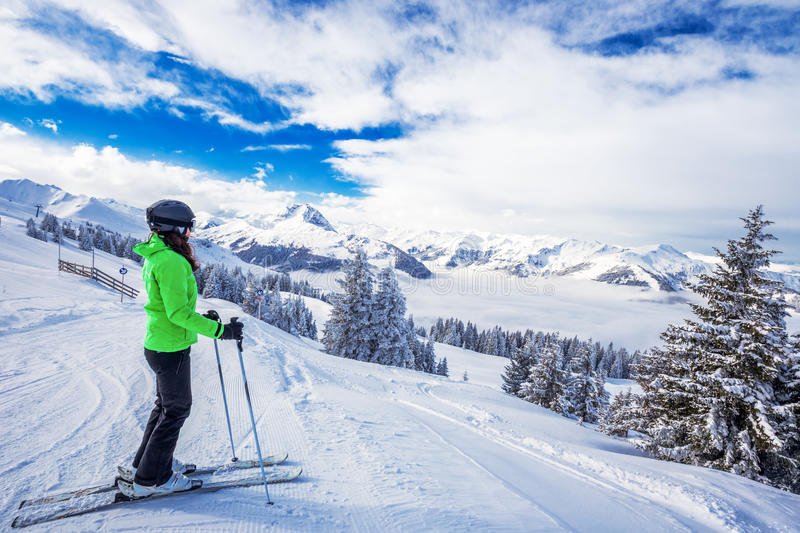 Young woman skiing in Kitzbuehel ski resort and enjouing the beautiful weather with blue sky and Alpine mountains in Austria. royalty free stock image