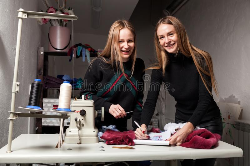 Young woman skinner. Close-up, two furrier women smile and discuss how to cut a fur coat from natural fur, on the table lie fur samples and a sketch of a fur royalty free stock photo