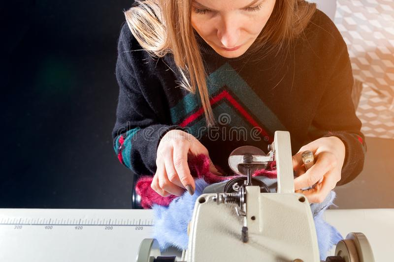 Young woman skinner. Close-up of a young furrier woman will process natural fur on a sewing machine to make a woman`s fur coat, top view stock images