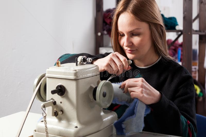 Young woman skinner. Young woman Furrier sewing blue fur coat on sewing machine in workshop stock images