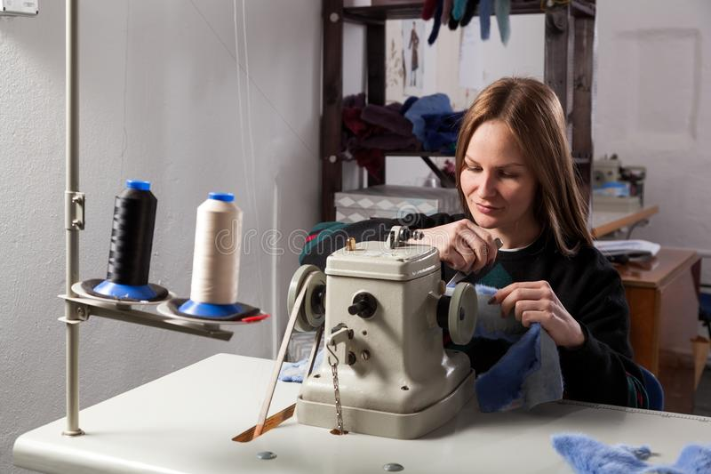 Young woman skinner. A young cheerful woman furrier smiles and sews a bright fur coat of natural blue fur on a sewing machine in the workshop stock photos