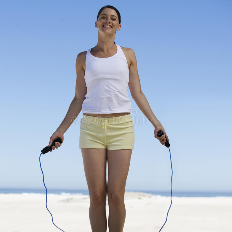 A young woman skipping on a beach royalty free stock images