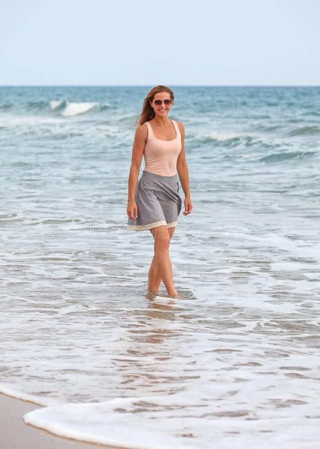 Young woman in skirt, t shirt and sunglasses standing in shallow water on the beach during overcast day, sea behind her stock photo