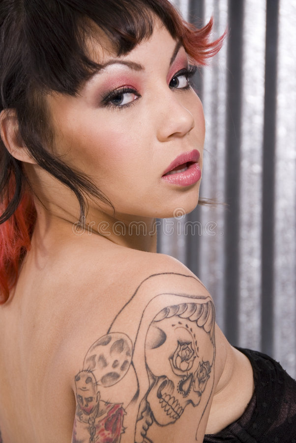 Young woman with skull tattoo. Portrait of a beautiful woman with skull tattoo. Dramatic make up done by a professional make up artist stock image