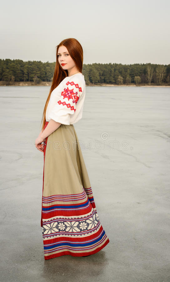 Young woman in Slavic Belarusian national original suit outdoors royalty free stock photo
