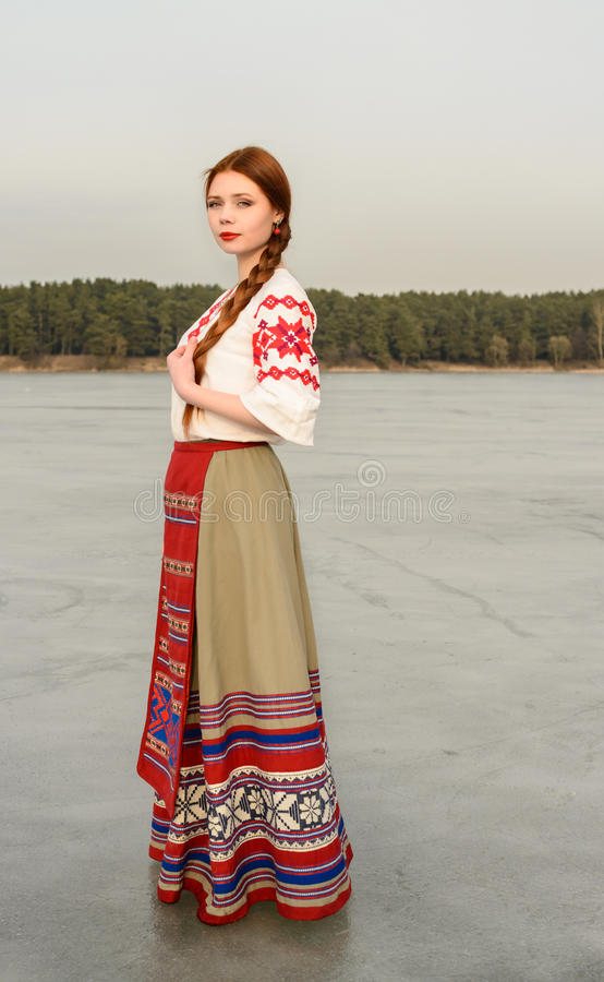 Young woman in Slavic Belarusian national original suit outdoors stock photo