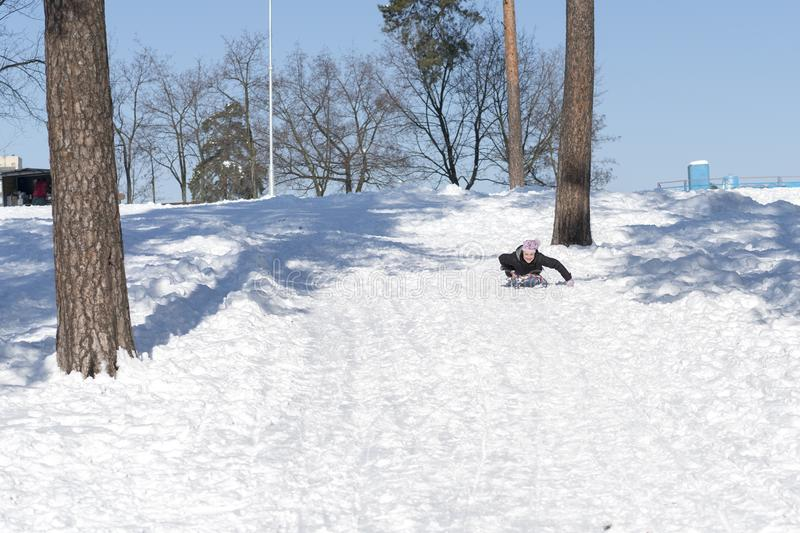 Young woman sledding in snow. laughing girl in winter clothing goes down on sleds down the hill.  stock photography