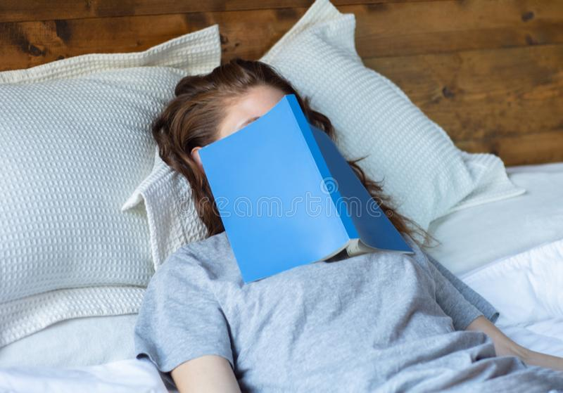 Young woman sleeping on bed with book stock images