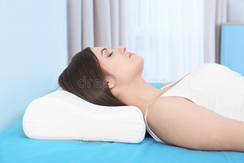 Young woman sleeping on bed with orthopedic pillow. At home. Healthy posture concept stock photo