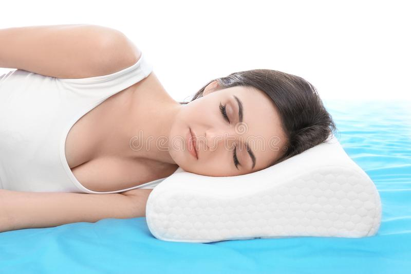 Young woman sleeping on bed with orthopedic pillow. Against white background. Healthy posture concept stock photos