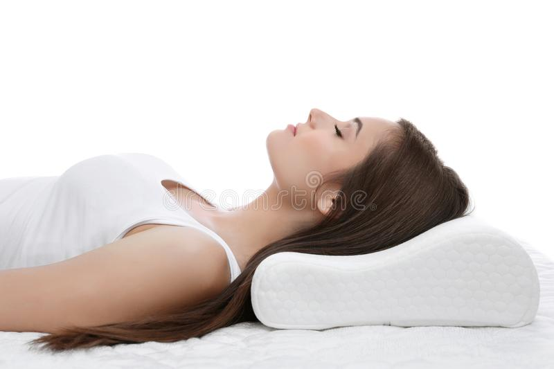 Young woman sleeping on bed with orthopedic pillow. Against white background. Healthy posture concept royalty free stock photo