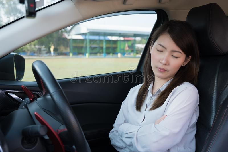 Young woman sleeping in car stock photo