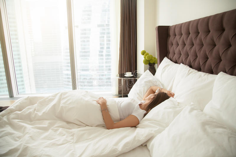 Young woman sleeping. Comfortably, quality bed linen and bedding, staples quilts and pillows, drank too much the night before, too lazy to shower, having her stock photo