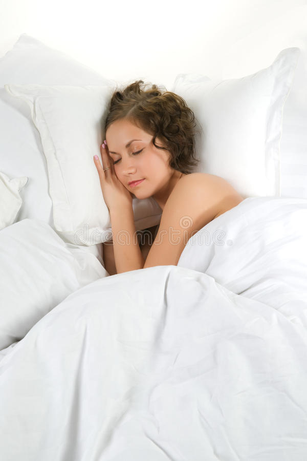 Young woman sleeping in a soft bed stock images