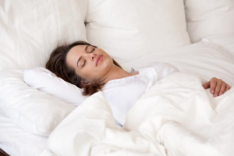 Young woman sleeping well in cozy bed with white linen. Young woman sleeping well in cozy comfortable bed on orthopedic mattress pillows with cotton luxury linen stock photos