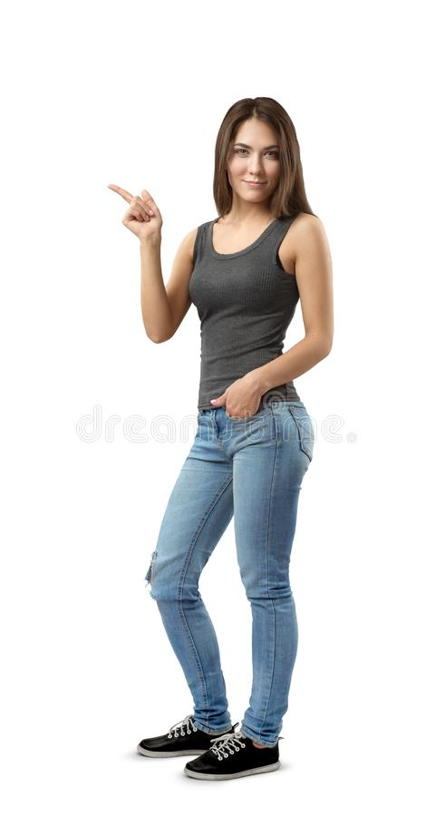 Young woman in sleeveless top and jeans standing in half-turn with left hand in pocket and right hand pointing sideward royalty free stock images