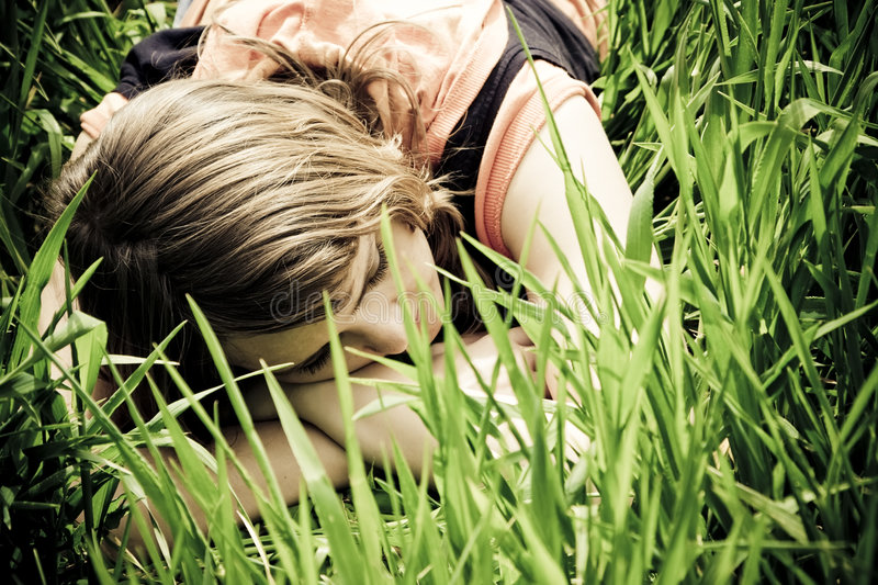 Young woman slept on the grass. Young slept woman trough the grass stock images