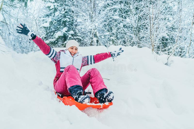 Young woman slide down from snow slope sitting in one slide.Winter activities concept image stock photos