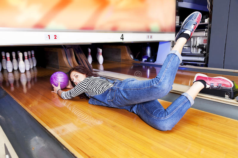 Young woman sliding down a bowling alley. Attached to the ball stock photo