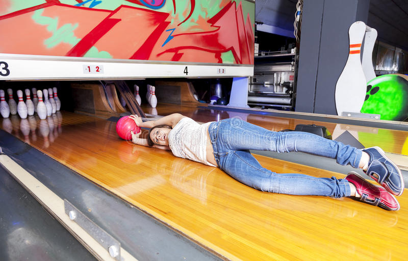 Young woman sliding down a bowling alley. Attached to the ball royalty free stock image
