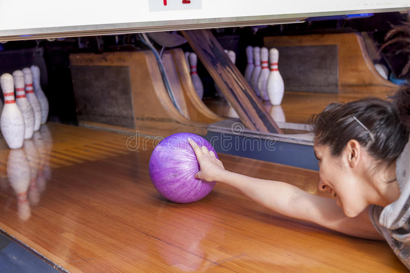 Young woman sliding down a bowling alley. Funny young woman sliding down a bowling alley stock images