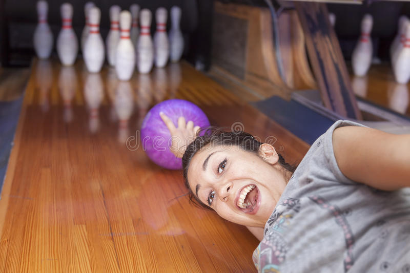 Young woman sliding down a bowling alley. Funny young woman sliding down a bowling alley stock photography