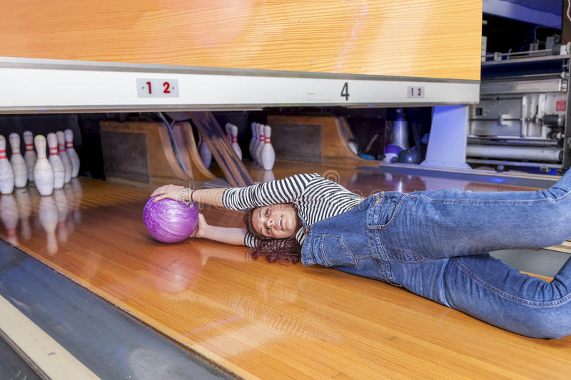 Young woman sliding down a bowling alley. Funny young woman sliding down a bowling alley stock photos
