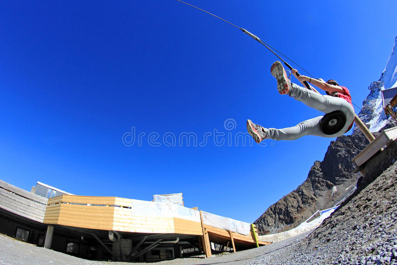 A young woman slips on a zipline stock images