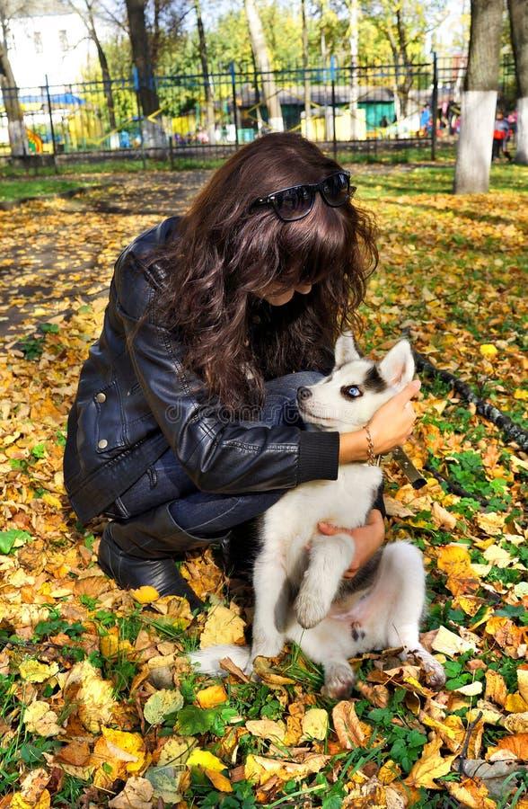 Young woman and  small dog siberian husky