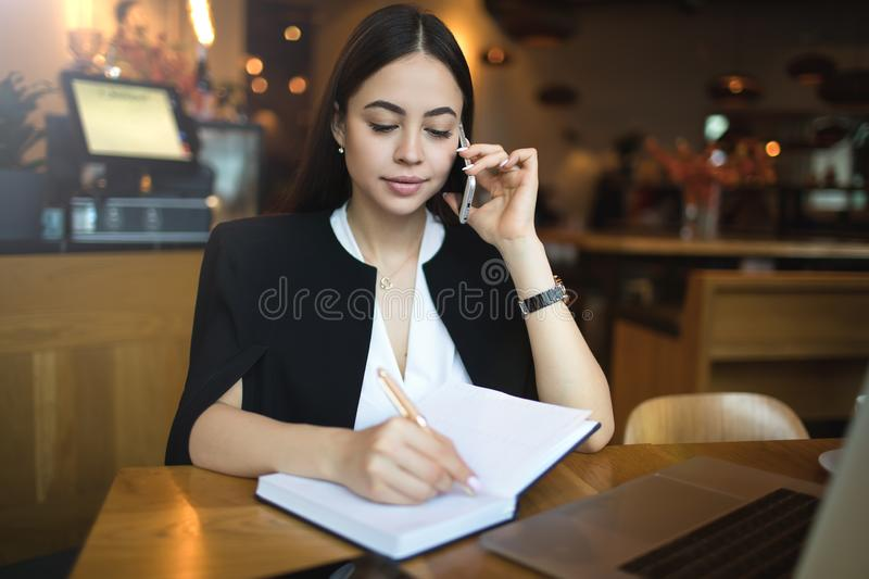 Young woman smart university student writing information in textbook during mobile phone conversation royalty free stock photos