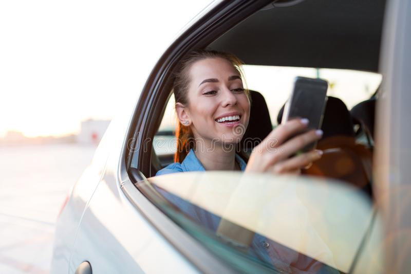 Woman with phone on the back seat of a car stock images