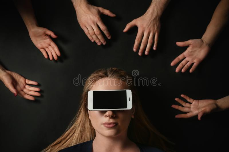Young woman with smartphone covering her eyes surrouded by people`s hands on black background, top view stock photography