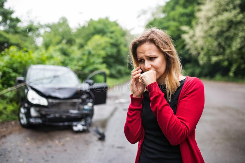 A young woman with smartphone by the damaged car after a car accident, making a phone call. royalty free stock images